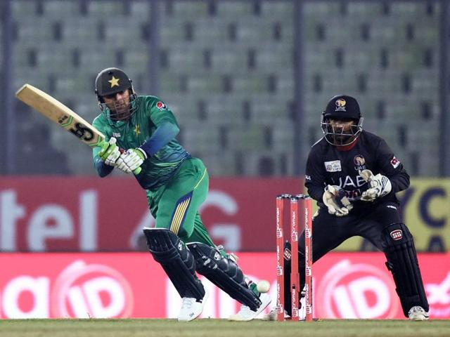 Pakistan's Shoaib Malik (L) plays a shot as United Arab Emirates' wicketkeeper Swapnil Patil (R) looks on.