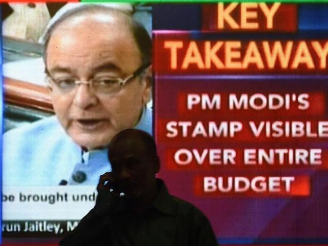 An office worker walks past a digital screen at the Bombay Stock Exchange (BSE) in Mumbai showing finance minister Arun Jaitley delivering the budget speech in Parliament.