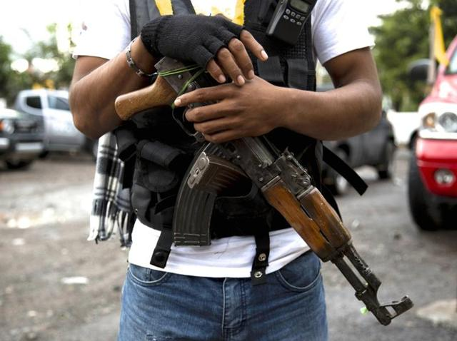 A vigilante member stands guard in Tierra Blanca. The murder of the five young men has sparked fears that yet another case of corrupt police officers are in league with the vicious drug cartels of Mexico.