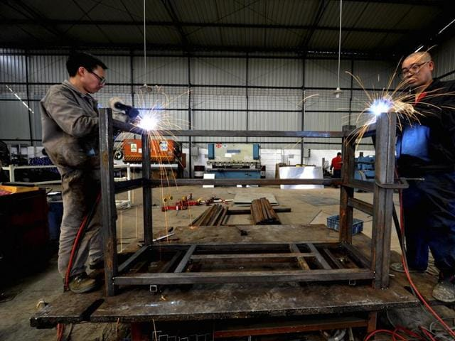 Workers weld steel frames for the Toyota Motor Corporation at a factory in Longquan in Chengdu in southwestern China's Sichuan province. China's manufacturing lost momentum again in February.