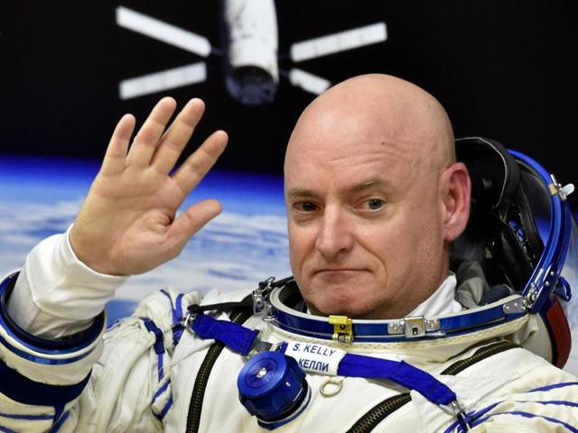 US astronaut Scott Kelly waves as his space suit is tested at the Russian-leased Baikonur cosmodrome, prior to blasting off to the International Space Station (ISS).  Kelly and his Russian counterpart, Mikhail Kornienko, will return to Earth after spending nearly a year in space.