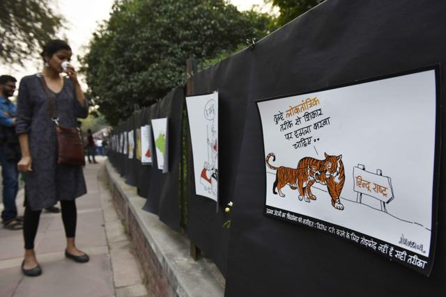 Cartoonist Gopal Shonya with his creations on display on the grills of Park in Front of Admin Block at JNU Campus in New Delhi , India, on Tuesday, March 1, 2016.