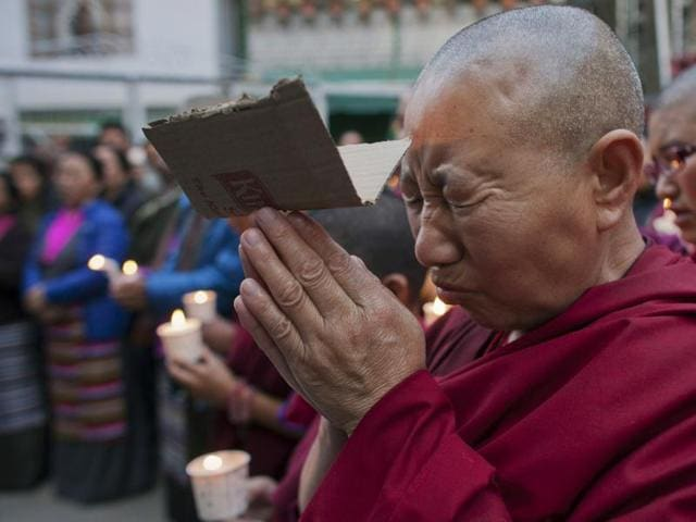 An exiled Tibetan carries a portrait of the Dalai Lama while another holds a poster with portraits of two Tibetans who exiles claim immolated themselves demanding freedom for Tibet, during a candle-light vigil in Dharmsala on Wednesday.