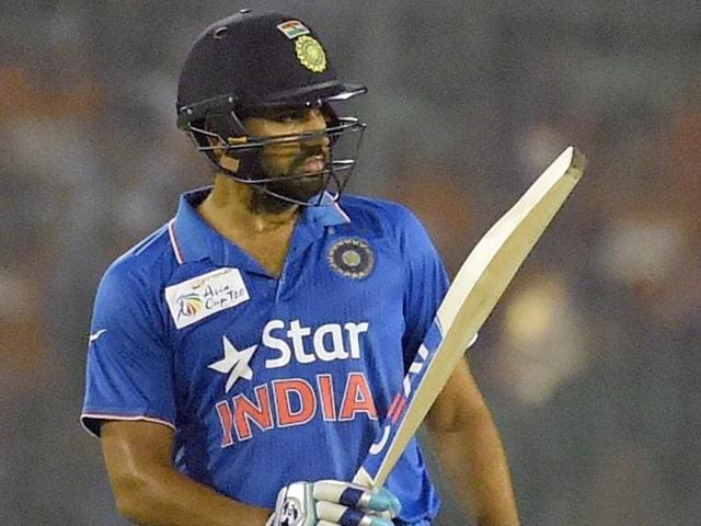Indian cricketer Rohit Sharma acknowledges the crowd after scoring a half century against Bangladesh.