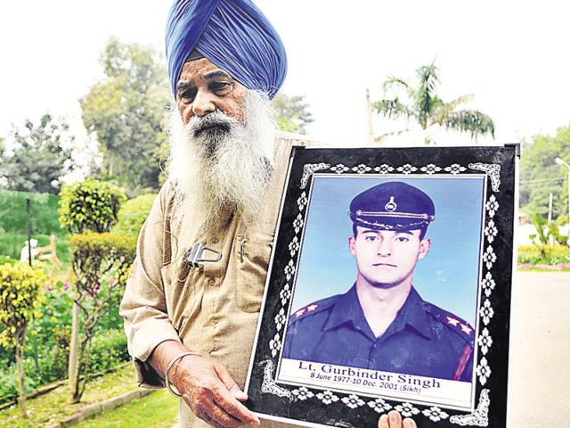 Ajit Singh, father of Kargil martyr Lt Gurbinder Singh, holding a picture of his son.