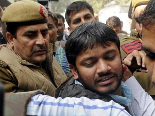 A policeman tries to save a JNU student who was being beaten up during a clash between the advocates and the students outside the Patiala House Courts in New Delhi . The clash broke out after a protest by the students against the arrest of JNU student leader Kanhaiya Kumar.