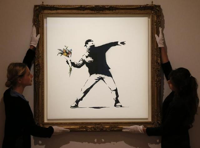 In this Monday, June 24, 2013 file photo, Bonhams employees adjust a spray paint work by urban artist Banksy at Bonhams auction house in London.