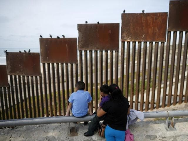 A family looks towards metal bars marking the United States border where it meets the Pacific Ocean in Tijuana, Mexico.