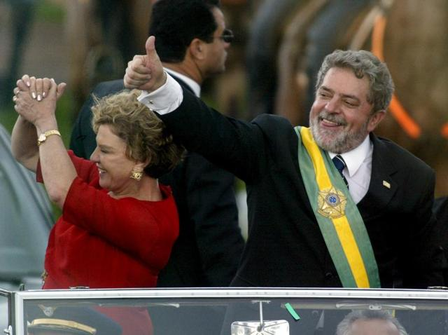 Brazil's new president Luiz Inacio Lula da Silva (R) gestures to thousands of followers as he rides past them with his wife, Marisa, after he received the presidential sash, in Brasilia, Brazil, in this January 1, 2003 file photo.