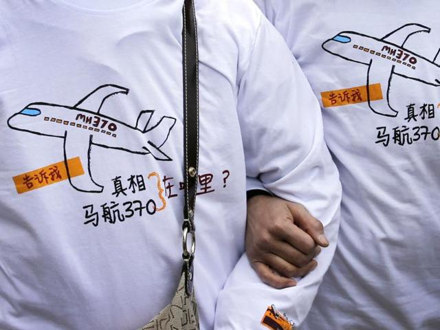In this file photo, relatives of passengers on board the Malaysia Airlines Flight 370 are seen wearing T-shirts carrying a message for the missing flight.