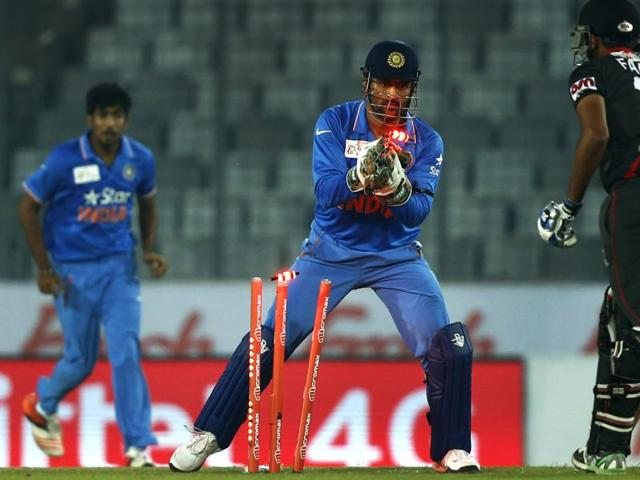 India's captain Mahendra Dhoni takes the wicket of United Arab Emirates' Farhan Ahmed.