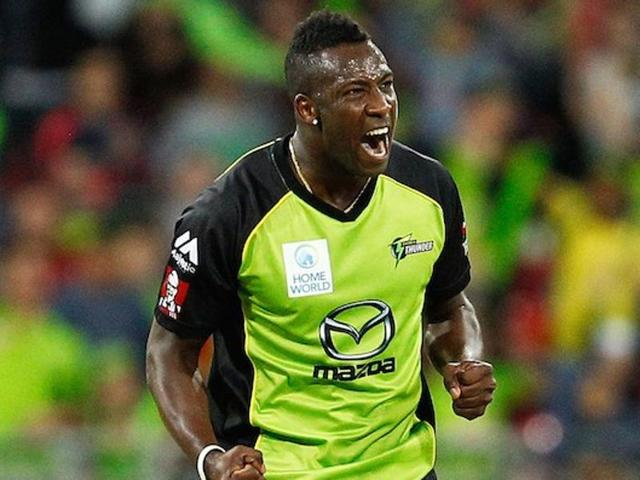 Andre Russell of the Thunder celebrates after claiming the wicket of Brad Hodge of the Strikers.