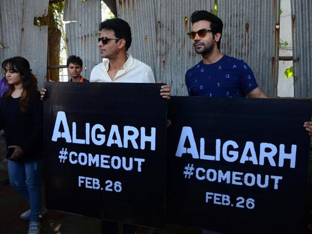 Actors Rajkummar Rao and Manoj Bajpai hold banners of their upcoming movie 'Aligarh' during a promotional event in Mumbai.