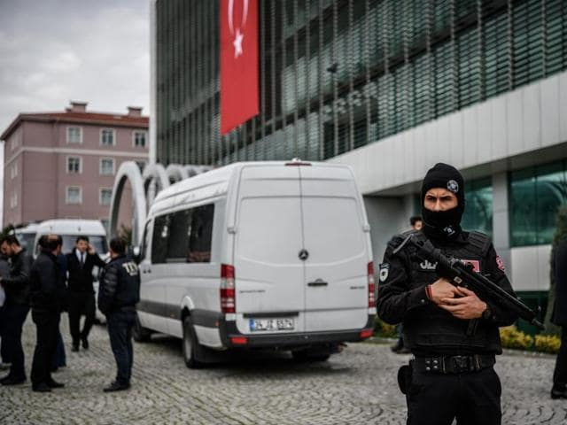 Turkish anti-riot police officers stand guard in front of the headquarters of Turkish daily newspaper Zaman in Istanbul.