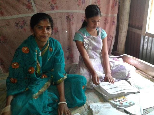 Smriti Banik studying for the ongoing matriculation examinations with her daughter at Purba Laxmibil village in Tripura.