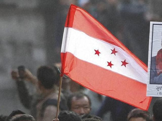 A supporter holds the Nepali congress Party flag during the cremation of Nepalese prime minister Sushil Koirala, in Kathmandu, Nepal. The party will vote to elect its new leadership on Sunday.