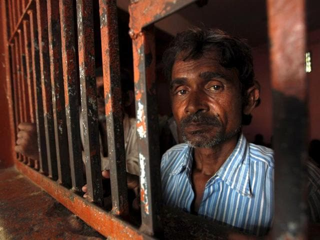 A fisherman from India looks on from behind the bars of his cell at a police station in Karachi, Pakistan, October 5, 2015.