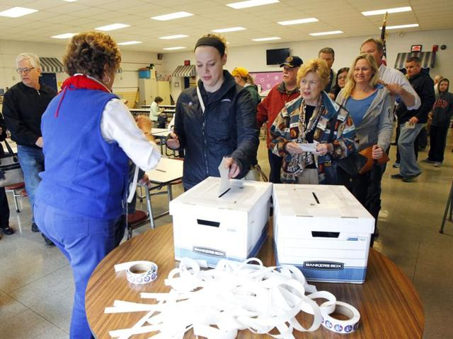 Kentucky voters place their paper ballots in voting box in the GOP presidential caucus at Zachary Taylor Elementary school.