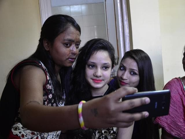 Acid attack victims pose with TV actress Amita Nangia during a fashion show in Bhopal on Sunday.