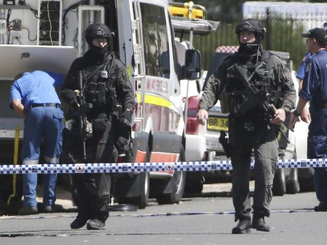 Police Tactical Group officers walk on a cordoned off street of an industrial section of Ingleburn in Sydney.