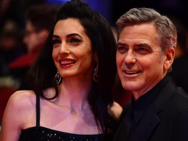 US actor George Clooney (R) and his wife Amal Alamuddin pose for photographers as they arrive on the red carpet for the film Hail, Caesar!