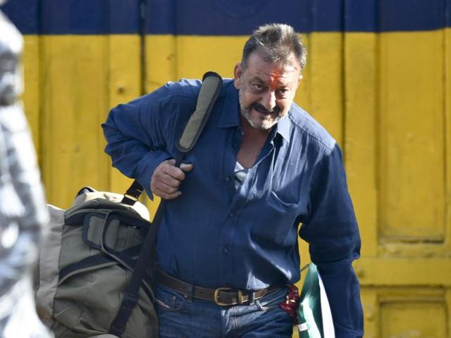 Indian Bollywood actor Sanjay Dutt waves as he is escorted by officials from Yerwada Jail in Pune.
