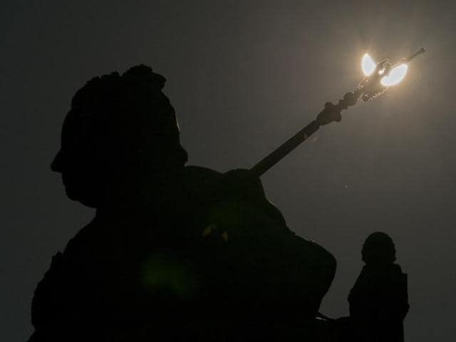 A partial solar eclipse is visible over a statue located at the rooftop of the Museum of Natural History in Vienna on March 20, 2015.