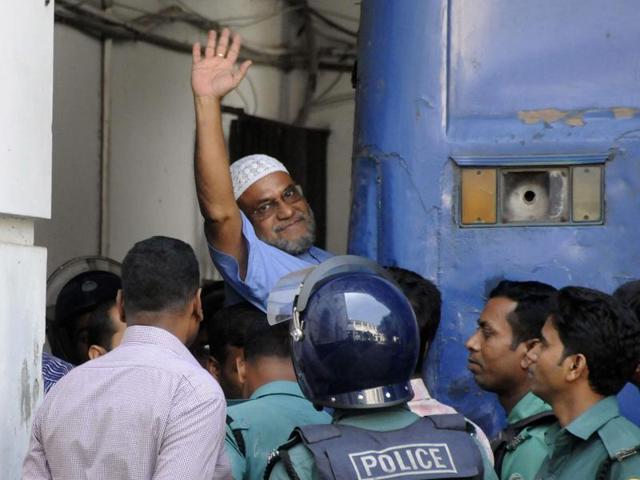 This file photo shows Bangladeshi Jamaat-e-Islami party leader, Mir Quasem Ali waving his hand as he enters a van at the International Crimes Tribunal court in Dhaka.