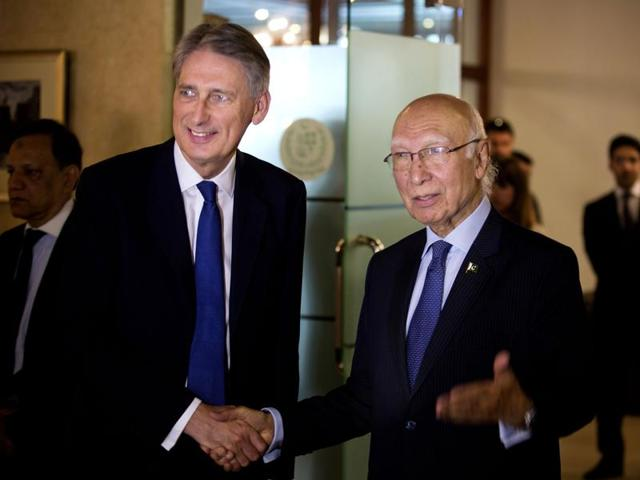 Pakistan Prime Minister's advisor on Foreign Affairs Sartaj Aziz(R)and British Foreign Secretary Philip Hammond (L) shake hands at a joint press conference in Islamabad on March 8, 2016.