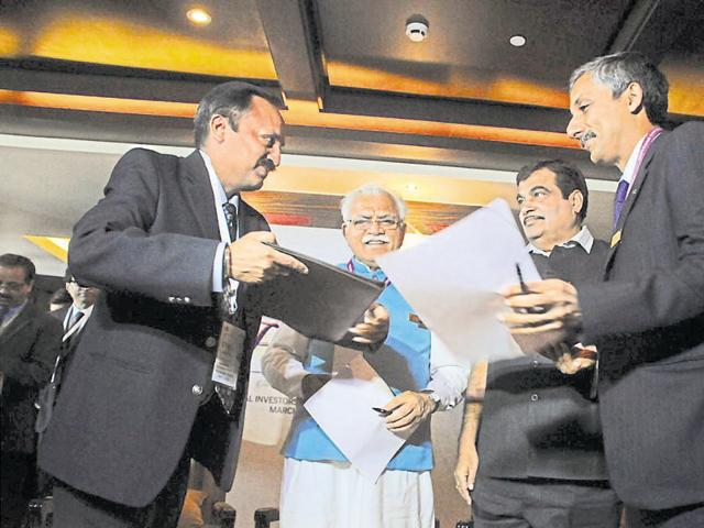 MD of Haryana State Industrial and Infrastructure Sudhir Rajpal (right) exchanges an MoU with an investor in the presence of Haryana CM Manohar Lal Khattar and Union minister Nitin Gadkari.