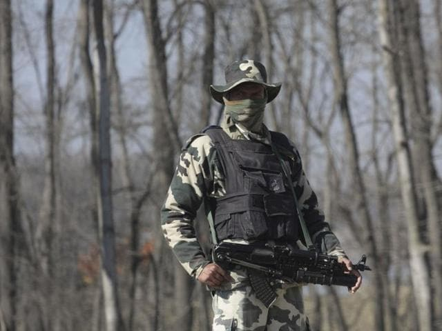 A paramilatary soldier stands guard near the site of an encounter with militants in a village in Pulwama district.