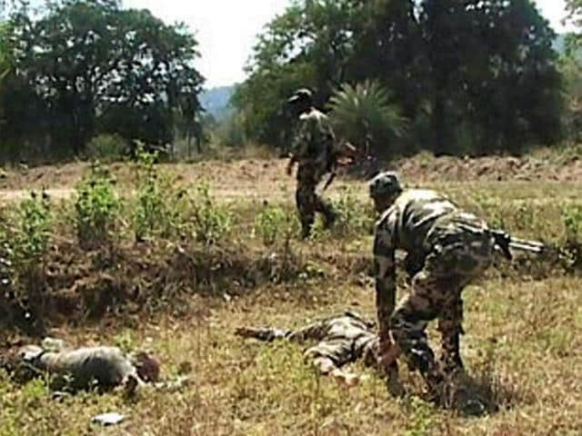 Security personnel check the bodies of their colleagues killed in a Maoist attack in Sukma district.