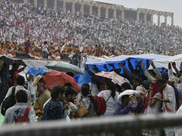 People are seen covering themselves with umbrellas and plastic sheets at the World Culture Festival venue in New Delhi.