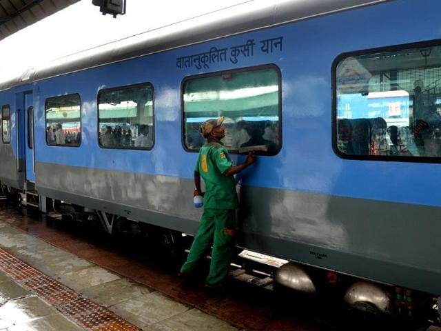 A railway worker cleans a coach prior to the trial run of a high-speed train between New Delhi and Agra.