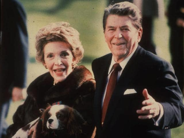 This December 1986, file photo shows first lady Nancy Reagan holding the Reagans' pet Rex, a King Charles spaniel, as she and President Reagan walk on the White House South lawn.