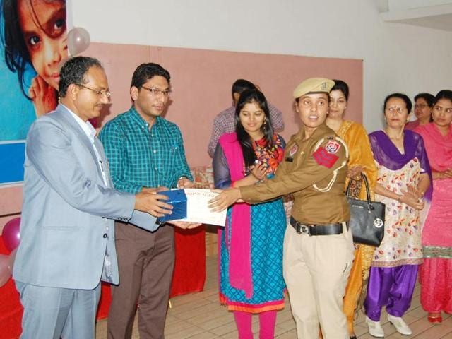 Deputy commissioner Varinder Sharma honouring a woman constable in Mansa on Thursday.