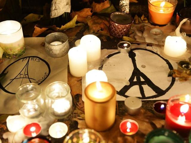 This photo taken on November 16, 2015 shows candles and messages left at a makeshift memorial next to the Bataclan concert hall in Paris. Islamic State jihadists claimed a series of coordinated attacks by gunmen and suicide bombers in Paris that killed at least 129 people in scenes of carnage at a concert hall, restaurants and the national stadium.