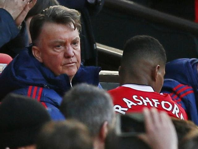 Manchester United's English striker Marcus Rashford (L) shakes hands with Dutch manager Louis van Gaal (C) during the English Premier League football match between Manchester United and Arsenal at Old Trafford.