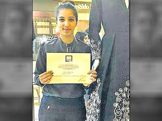 Sherry Khanna posing with her ceritificate near the gown that was designed by her.