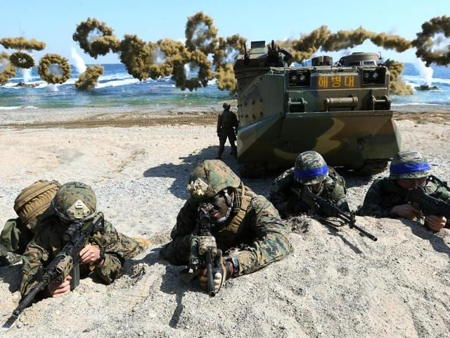 US Marines, left, and South Korean Marines, wearing blue headbands on their helmets, take positions after landing on the beach during the joint military combined amphibious exercise, called Ssangyong, part of the Key Resolve and Foal Eagle military exercises, in Pohang, South Korea.