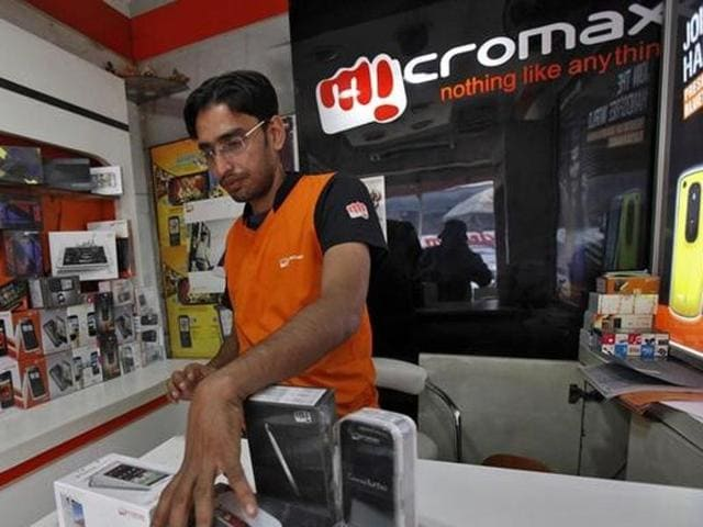 A worker displays a Micromax mobile phone inside a store in Kolkata