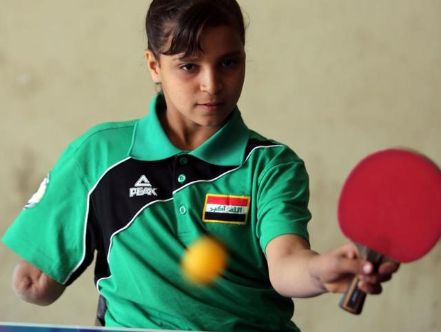 Twelve-year-old disabled Iraqi Nejla Imad plays table tennis in Baquba.
