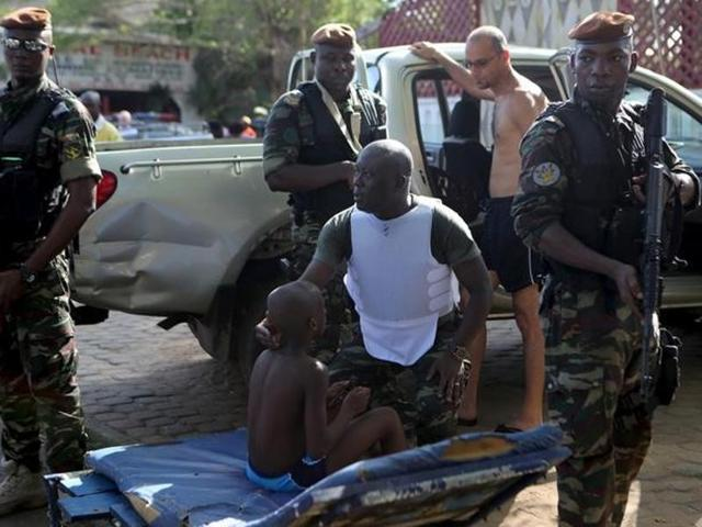Ivorian security forces evacuate people after heavily armed gunmen opened fire on March 13, 2016 on beach goers in the Ivory Coast beach resort of Grand-Bassam.