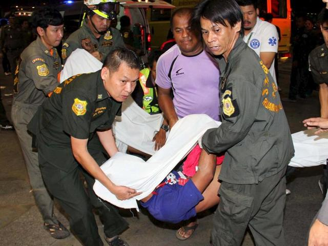 Rescue workers carry victims after a chemical accident started a fire at the headquarters of Thailand's Siam Commercial Bank, in Bangkok.