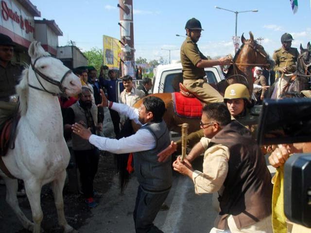 BJPMLA Ganesh Joshi hitting a horse during a party  rally at Vidhan Sabha in Dehradun, India, on Monday, March 14, 2016.