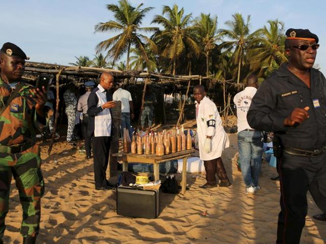Emergency workers and security officers gather on the beach after an attack in Grand Bassam, Ivory Coast.