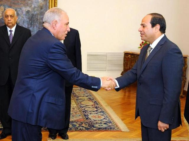 A file picture from 2015 shows Egyptian President Abdel Fattah al-Sisi (right) shaking hands with justice minister Ahmed al-Zind during his swearing-in ceremony in Cairo.