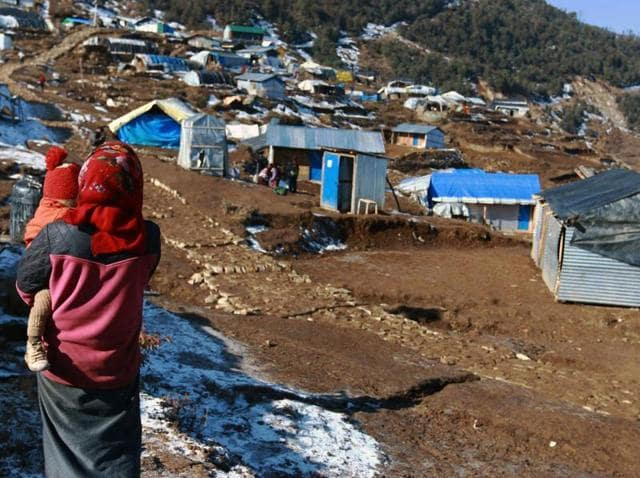 This photo taken on January 21, 2016 shows a woman and her child near temporary shelters in the Nepalese village of Laprak. Eleven months after a massive earthquake hit Nepal, thousands of survivors are awaiting government help to rebuild their homes.