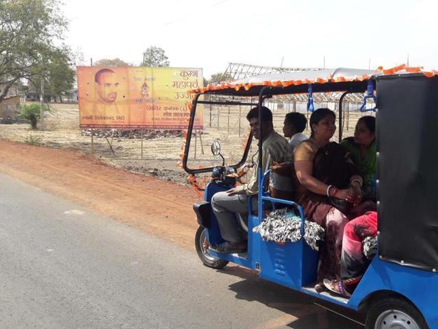 People travelling to Simhastha venue on a battery-operated auto rickshaw. Akhara camps have come up on either sides of the road at the fair venue.
