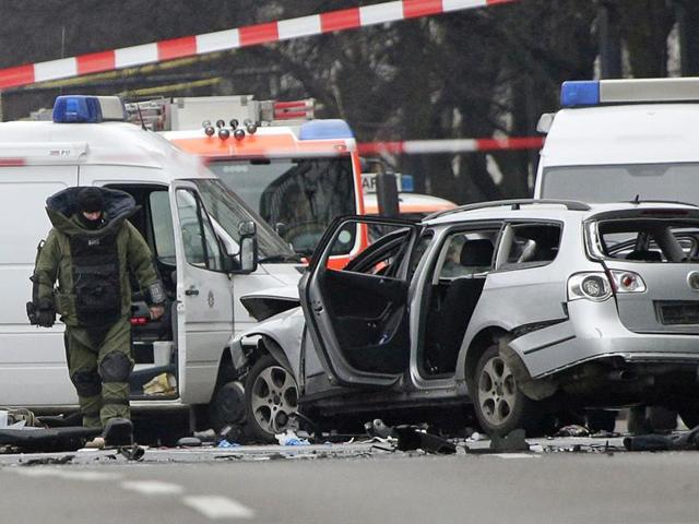 A bomb disposal specialist in protective gear passes by an exploded car as he investigates the site of the blast in Berlin, eastern Germany.